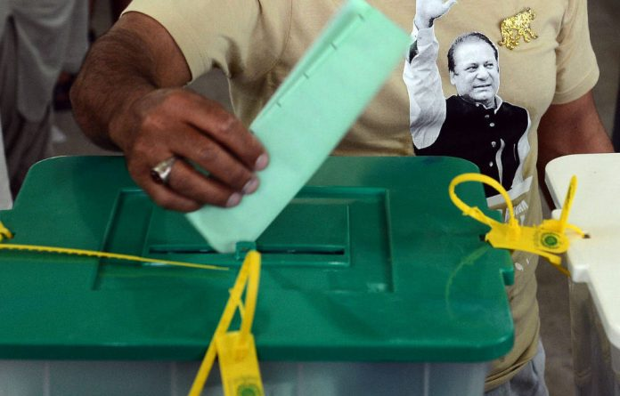 A supporter of former Pakistan prime minister Nawaz Sharif casts his vote at a polling station in Lahore.