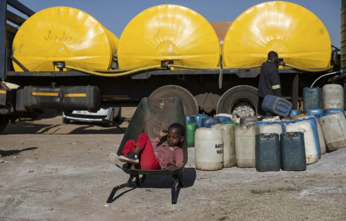 Six-year-old Malume Mashilo waits in the wheelbarrow his siblings will use to transport containers of water from a tank that has just been filled.