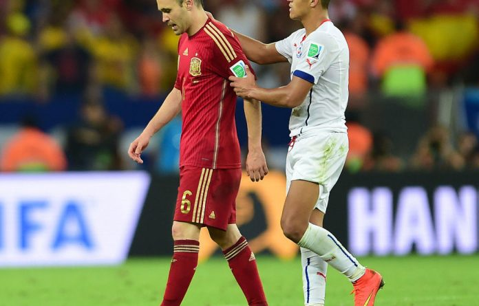 Chile's Alexis Sánchez comforts Spain's Andrés Iniesta after the champions' World Cup loss.