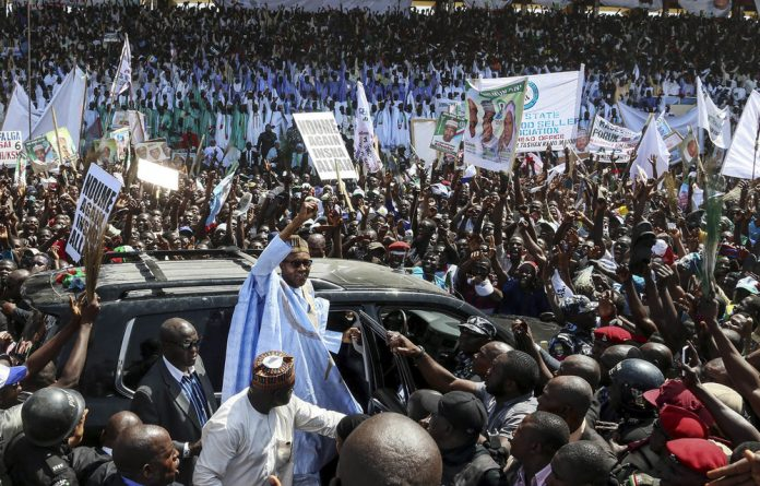 Muhammadu Buhari waves to his supporters as he arrives for an election campaign rally in Maiduguri