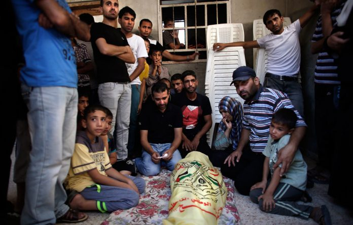 Relatives of the al-Kaware family mourn at the funeral of one of the seven members killed in Khan Yunis.