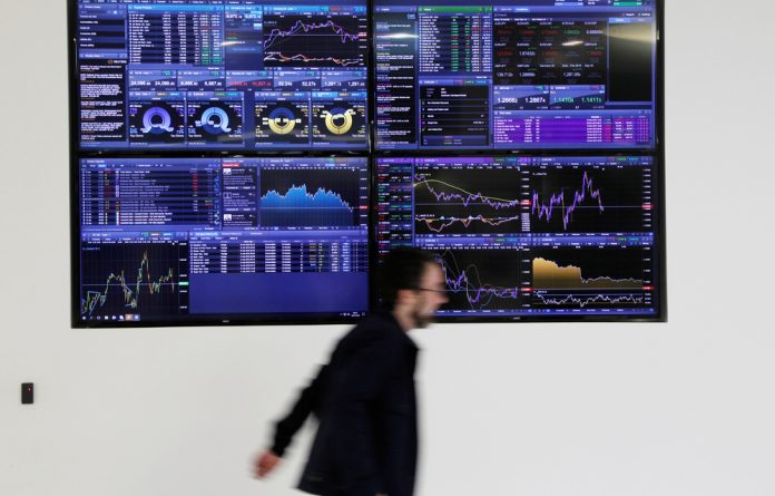 A man walks past screens displaying market data at CMC Markets in London.