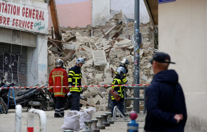 French rescue workers are seen near rubble after buildings collapsed in central Marseille
