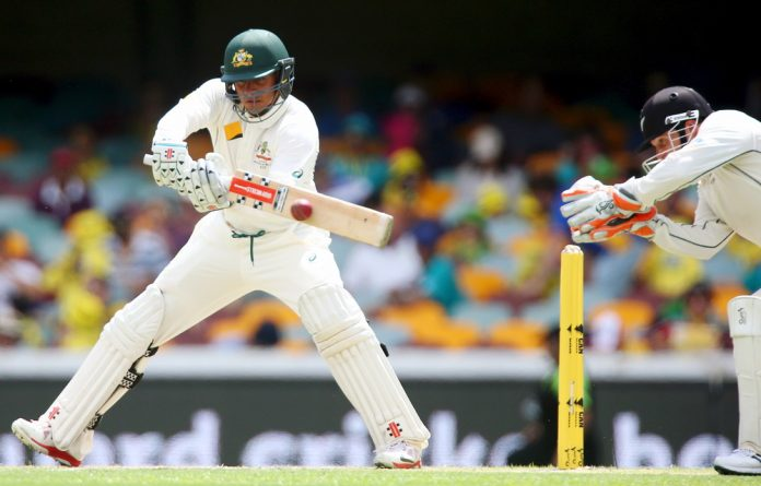 Australian batsman Usman Khawaja drives a wide delivery for 4 runs during the first cricket test match between Australia and New Zealand in Brisbane November 6