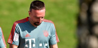 Franck Ribery walks across the training area with his smartphone before the start of a training session of his club in the morning.