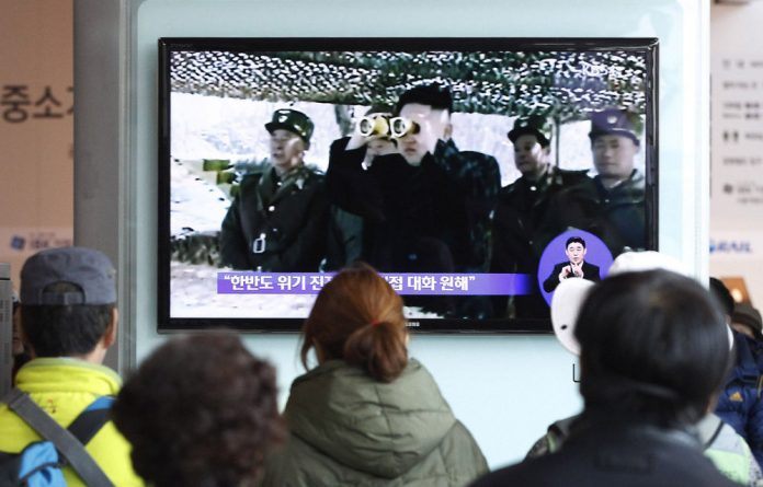 South Koreans watch a TV screen at the Seoul railway station on April 7.