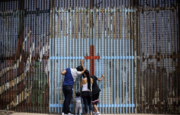 A family talks to relatives through the US-Mexico border fence in Playas de Tijuana