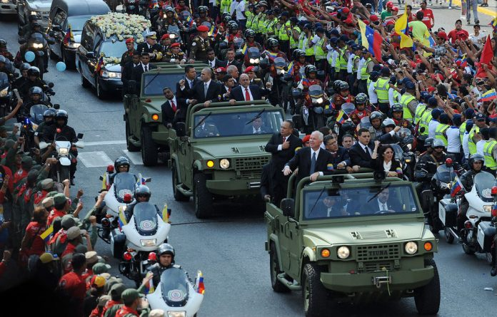 Venezuelan Government authorities and guests ride vehicles in front of the hearse carrying the remains of late Venezuelan President Hugo Chavez to his resting place.