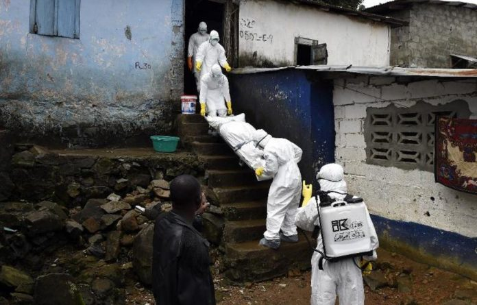 Medical workers carry a body out of a building in Liberia. The worst outbreak of Ebola in the West Africa region has claimed more than 3 000 lives.