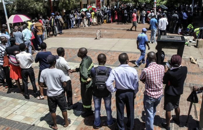 Cash-strapped: Zimbabweans queue to withdraw cash from a bank after the central bank introduced bond notes.