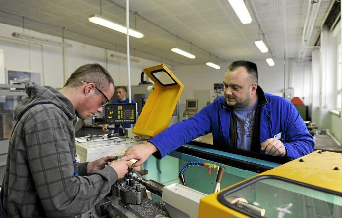 Instructor Thomas Olm guides a student at a retraining facility for the unemployed in the German town of Neubrandenburg.