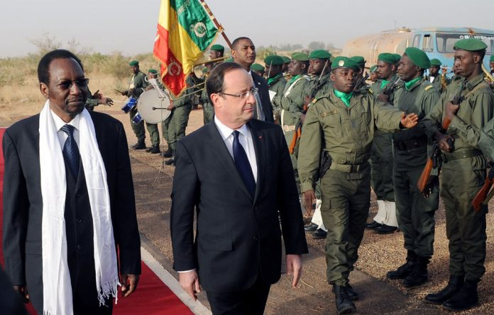 Francois Hollande is welcomed by Mali's interim president Dioncounda Traore upon his arrival at Sevare