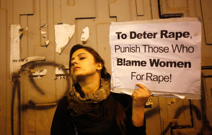 A demonstrator holds a placard as she attends a candlelight vigil in protest against the rape in Delhi.
