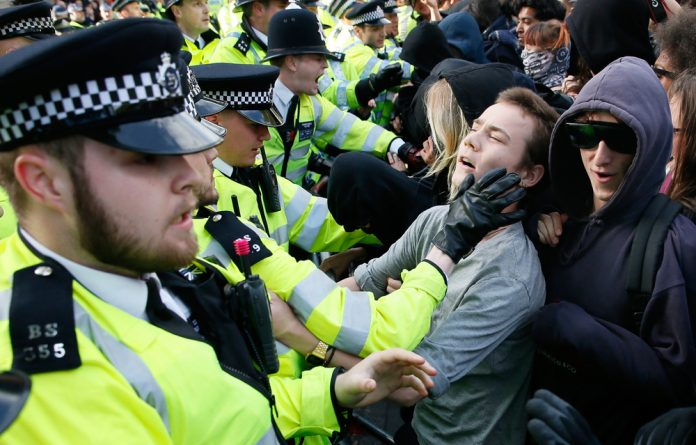 Protesters and police face off at the gates of Downing Street during a protest against the Conservative Party in central London.
