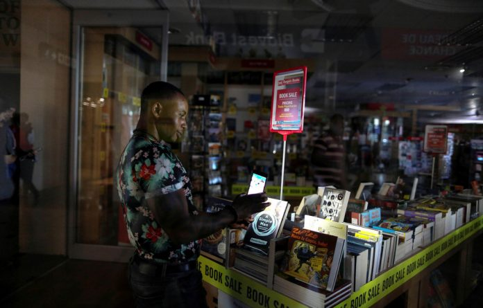 In the dark: An employee uses the light of his cellphone to pack away books during a blackout in Cape Town.