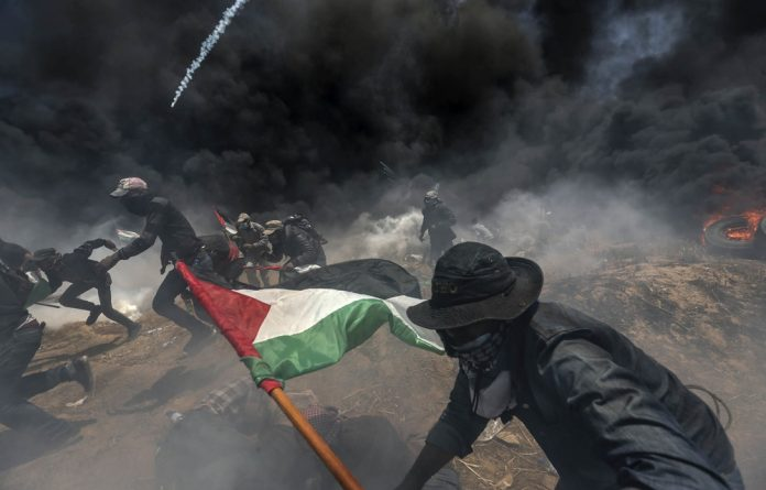 Unreal reality: Gazans run for cover from Israeli army gunfire and teargas during a protest against the United States moving its embassy to Jerusalem on the eve of al Nakba.