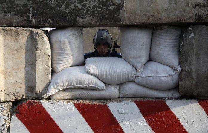 An Ukrainian policeman guards a checkpoint at the entrance of the southeastern Ukrainian city of Berdyansk.