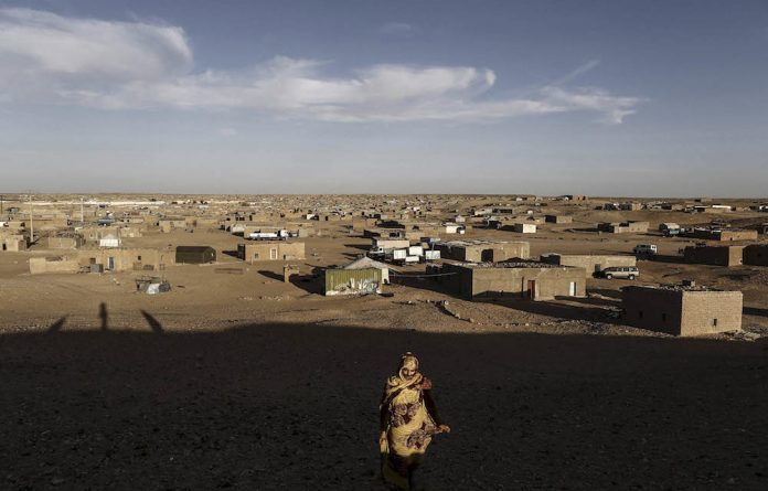 An indigenous Sahrawi woman walks at a refugee camp of Boudjdour in Tindouf