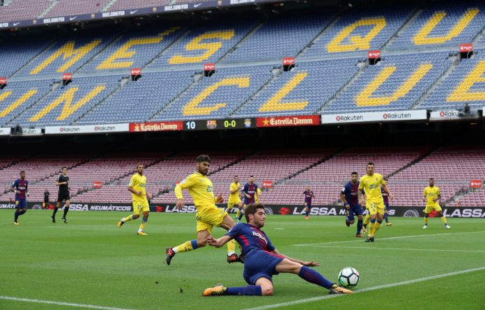 Barcelona's Sergi Roberto in action infront of an empty stadium as the game is played behind closed doors.