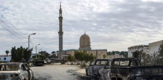 Devastation: Bombed and burnt-out cars line the road leading to the Rawda Mosque