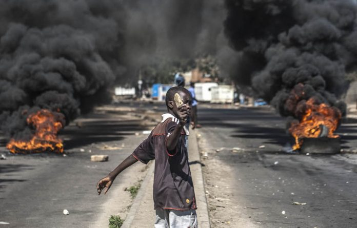 Burning issues: A protester throws rocks during a protest in Bulawayo.