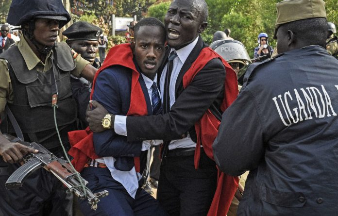 Fear: Students clash with police during a protest against the motion to scrap the presidential age limit — seen as a way for Museveni to seek a sixth term as leader