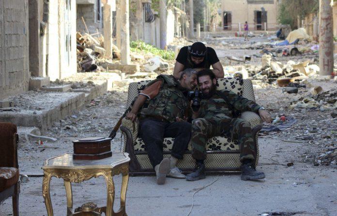 Free Syrian Army fighters take a break in Deir al-Zor on Friday.