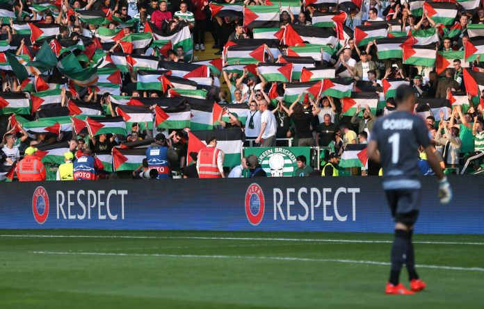 Celtic fans hold up Palestine flags during the Champions League match against Hapoel Be'er Sheva.