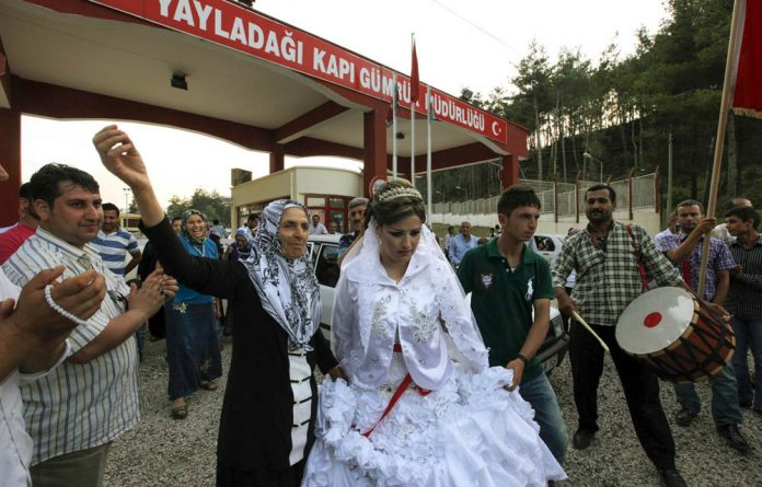 Syrian bride Reme is welcomed by family members of her Turkish groom
