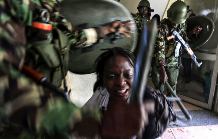 A student is beaten by riot policemen during a student protest in Kenya's capital Nairobi in 2014.