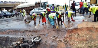 Nigerian workers clean the site of a bomb blast in Abuja on April 15 2014.