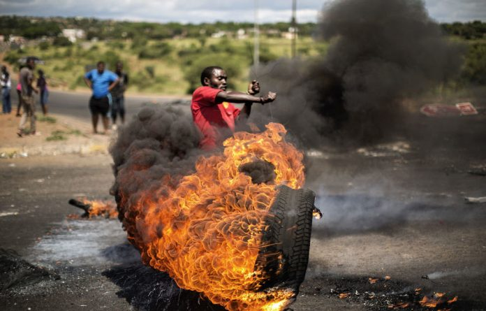 A demonstrator swings a burning tyre at a crossroad in Hebron during a protest for basic government services.