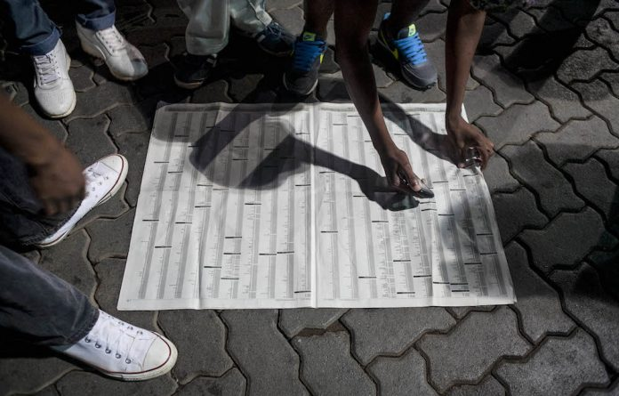 Matric learners searching for their names on newspapers during the release of the 2014 results at a service station in Dobsonville