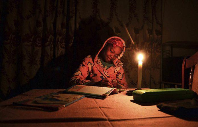 Grade six leaner Zandile Lebethe does her homework by candlelight in Johannesburg in September 2013. Like many