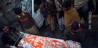 Pakistani volunteers transport the body of a charity worker following an attack by gunmen in Swabi on January 1 2013. Six women and a man were shot dead.