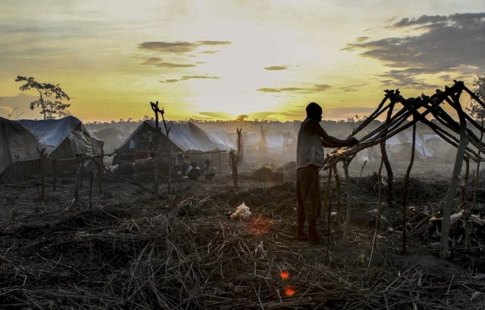 Refuge: A man builds a tent in the newly formed camp for internally displaced people in Kaga Bandoro.