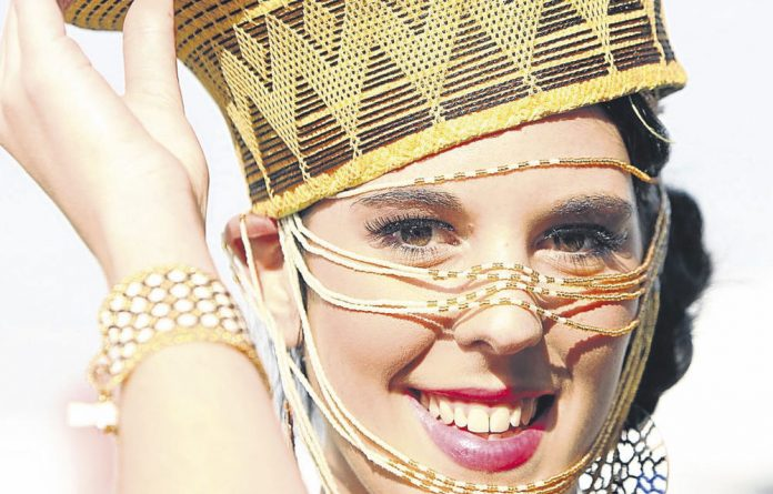 Carin Botha wears Sandiswa Sambiso at the Vodacom Durban July at Greyville Racecourse.