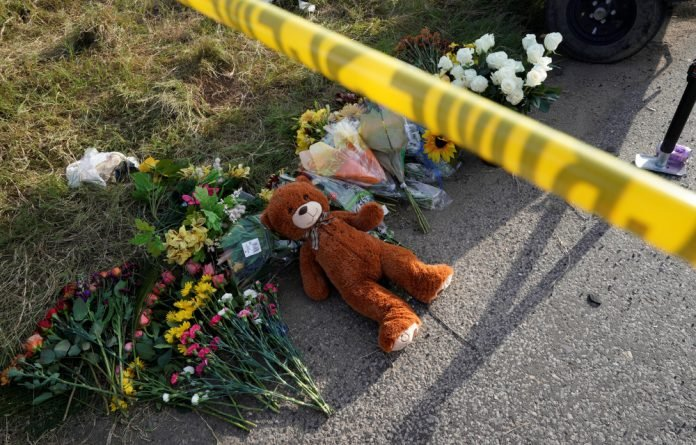A Teddy bear lies under police tape at a makeshift memorial for those killed in the shooting at the First Baptist Church of Sutherland