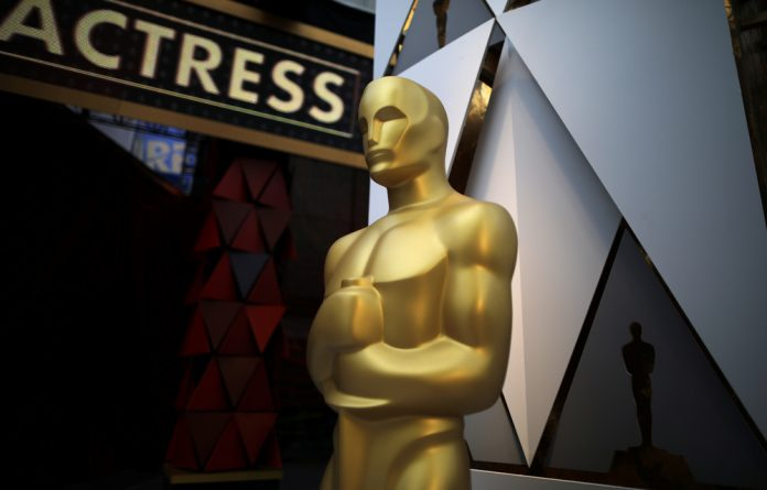 An Oscar statue is seen outside the Dolby Theatre during preparations for the Oscars in Hollywood