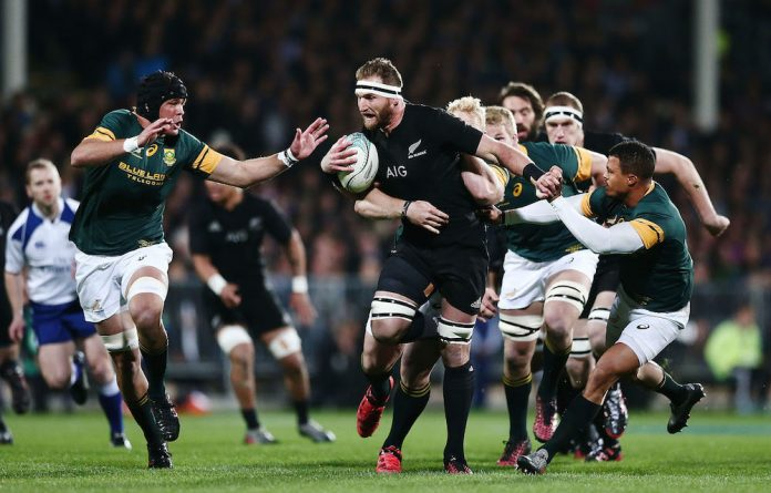 No stopping the All Black juggernaut: A herd of Springboks attempting to bring down the charging Kieran Reed.
