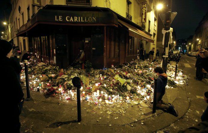 People pray outside Le Carillon restaurant