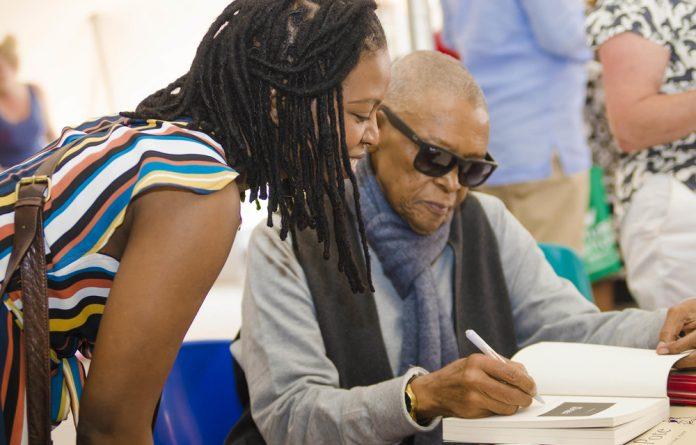 Bra Hugh Masekela signs a copy of his book Still Grazing: The Musical Joourney of Hugh Masekela