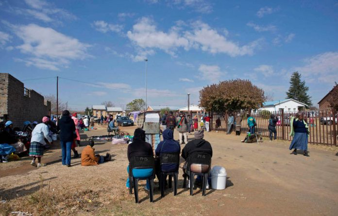 Three women who work for a loan shark wait for grant recipients at Thembalihle township in the Free State to repay the loans they have taken.