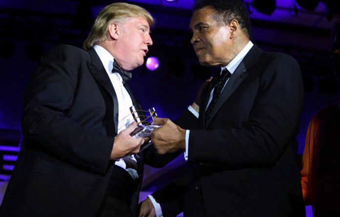 Donald Trump receives his award from Muhammad Ali during the boxer's Celebrity Fight Night XIII show in Phoenix