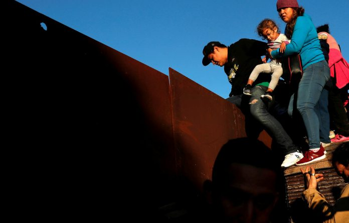 Keep out: Migrants climb over a border wall into the United States from Mexico.