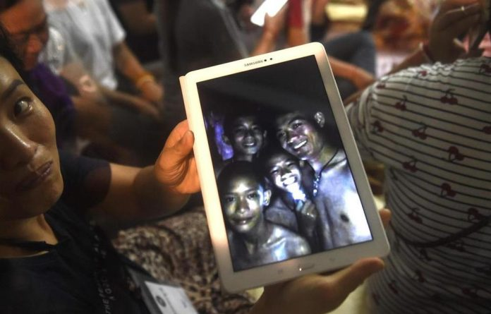 A happy family member showing a picture of the missing boys taken by rescue divers inside Tham Luang cave.