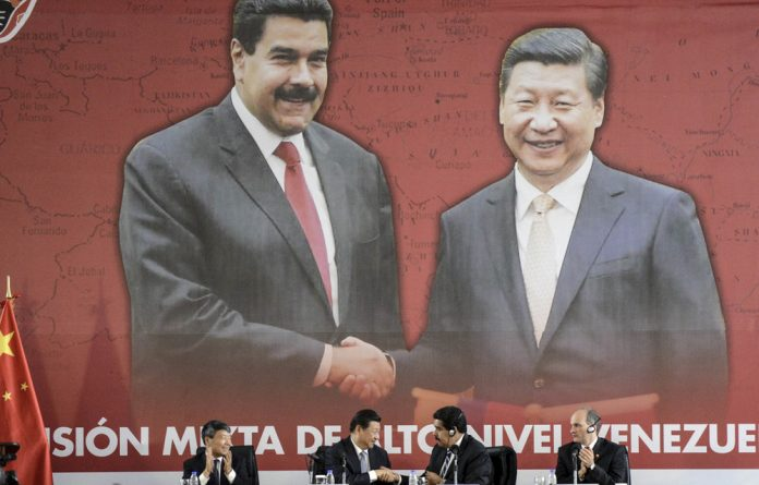 Vacuum: Venezuelan President Nicolás Maduro shakes hands with China's President Xi Jinping when agreements were signed in 2014. China has provided loans to more than 100 countries