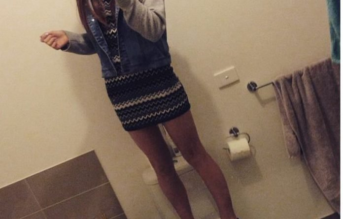 A girl takes a selfie while standing on the toilet.