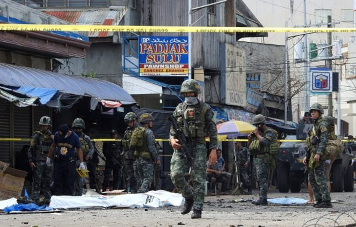 Policemen and soldiers keep watch in a cordoned area outside a church in Jolo