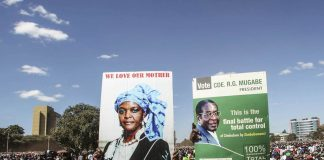 "Youths from the ruling Zanu-PF party hold portraits of President Robert Mugabe and his wife Grace during the ""One Million Man March"""